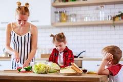 美丽的妇女的图象有她的烹调食物的女儿和儿子的在厨房里 库存图片