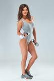美丽的妇女的完善的健身身体 -体育衣物的辅导员在灰色背景 库存图片