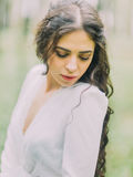 美丽的妇女的特写镜头画象看地面的白色婚礼礼服的在绿色森林里 库存图片