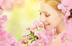 年轻美丽的妇女的秀丽面孔有桃红色花的在她的ha 免版税图库摄影