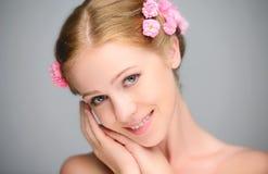 年轻美丽的妇女的秀丽面孔有桃红色花的 免版税库存图片