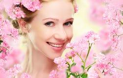 年轻美丽的妇女的秀丽面孔有桃红色花的 免版税库存照片