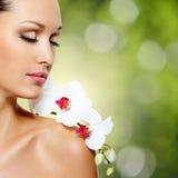 美丽的妇女的面孔有一朵白色兰花花的 免版税图库摄影