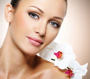 美丽的妇女的面孔有一朵白色兰花花的 库存照片