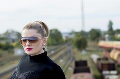 美丽的妇女的画象反对火车和铁路tr的 库存照片