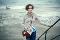 年轻美丽的妇女的画象皮靴的在海滩的银行 免版税库存照片