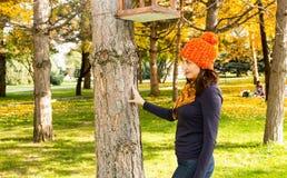 美丽的妇女秋天画象在黄色的在秋天的时公园离开,当走 正面情感和幸福概念 免版税库存照片