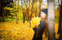 美丽的妇女秋天画象在黄色的在秋天的时公园离开,当走 正面情感和幸福概念 免版税库存图片