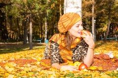美丽的妇女秋天画象在黄色的在秋天的时公园离开,当走 正面情感和幸福概念 免版税图库摄影
