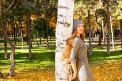 美丽的妇女秋天画象在黄色的在秋天的时公园离开,当走 正面情感和幸福概念 库存图片