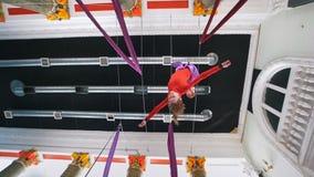 美丽的妇女空气体操运动员在空中丝绸垂悬颠倒 影视素材
