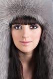美丽的妇女纵向冬天毛茸的帽子的 库存图片