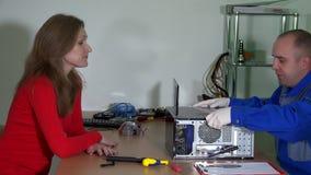 美丽的妇女给咨询的专业技术员人带来计算机 股票录像