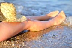 美丽的妇女腿和草帽在海滩在海水 免版税库存照片