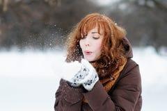 美丽的妇女获得乐趣在冬天 免版税库存图片