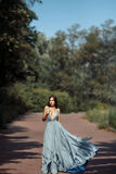 年轻美丽的妇女蓝色礼服人行道在公园 库存照片