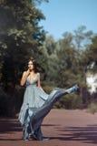 年轻美丽的妇女蓝色礼服人行道在公园 免版税图库摄影