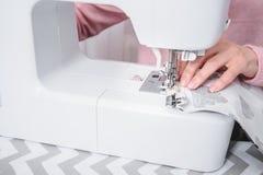 美丽的妇女裁缝在缝纫机衣裳缝合 免版税库存照片