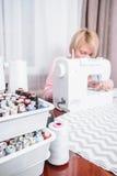 美丽的妇女裁缝在缝纫机衣裳缝合 库存照片