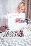美丽的妇女裁缝在缝纫机衣裳缝合 免版税图库摄影