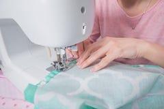 美丽的妇女裁缝在缝纫机衣裳缝合 免版税库存图片