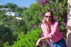 年轻美丽的妇女谈话与她的电话 图库摄影