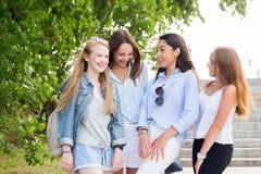 美丽的妇女谈话和笑在街道的小组在夏天步行期间 免版税图库摄影
