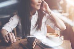 美丽的妇女谈话在咖啡馆的电话 巧克力蛋糕和咖啡在桌上 在咖啡馆的明亮的晴朗的早晨 库存图片