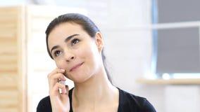 美丽的妇女谈话在智能手机在她的办公室 免版税图库摄影