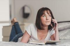 美丽的妇女谈话在智能手机在她的卧室 免版税库存照片