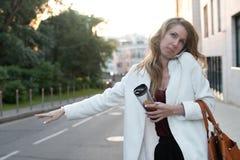 美丽的妇女谈话在走在街道上的电话 流行的服装的拜访M的时髦的微笑的女商人画象  免版税库存图片