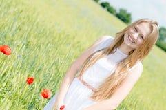 年轻美丽的妇女走在绿色麦田的愉快的微笑的&看的照相机在夏日 免版税库存照片