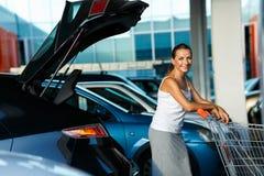 年轻美丽的妇女转移从购物车的购买  免版税库存图片