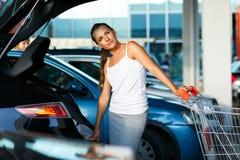 年轻美丽的妇女转移从购物车的购买  免版税图库摄影