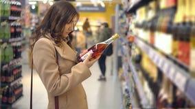 美丽的妇女选择在超级市场部门的桃红葡萄酒 影视素材