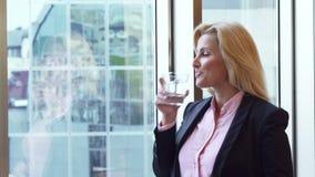 美丽的妇女通过她的办公室窗口看并且喝水 股票录像