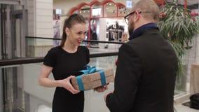 美丽的妇女采取从一个人的礼物黑夹克的 股票录像