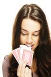 美丽的妇女采摘与她的牙的一个啤牌看板卡 免版税库存图片