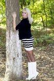美丽的妇女金发碧眼的女人在公园拥抱一棵树 免版税库存图片