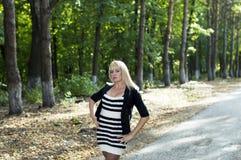 美丽的妇女金发碧眼的女人在公园走 库存图片