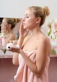 美丽的妇女金发碧眼的女人放置表面奶油 免版税库存照片
