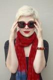 年轻美丽的妇女金发碧眼的女人画象红色围巾的,玻璃o 免版税库存照片