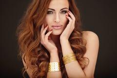美丽的妇女金黄画象  库存图片