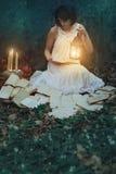 美丽的妇女阅读书在黑暗的森林里 库存照片