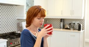 美丽的妇女食用咖啡在厨房4k 股票视频