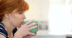美丽的妇女食用咖啡在厨房4k 影视素材