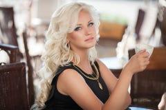 美丽的妇女饮用的咖啡在咖啡馆餐馆,酒吧的,暑假女孩。相当白肤金发在早餐。愉快的微笑的妇女 库存照片