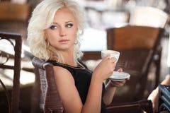 美丽的妇女饮用的咖啡在咖啡馆餐馆,酒吧的,暑假女孩。相当白肤金发在早餐。愉快的微笑的妇女 免版税图库摄影