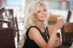 美丽的妇女饮用的咖啡在咖啡馆餐馆,酒吧的,暑假女孩。相当白肤金发在早餐。愉快的微笑的妇女 库存图片