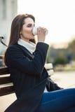 美丽的妇女饮用的咖啡坐在城市stree的一条长凳 库存照片